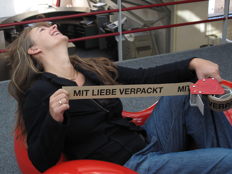 "Nina with the sticky paper tape ""Mit Liebe verpackt""."